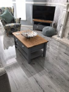 Coffee table and chair staged on high-gloss grey wood flooring