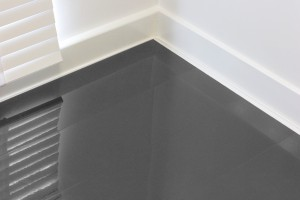 Graphite colored solid, high-gloss flooring against white walls