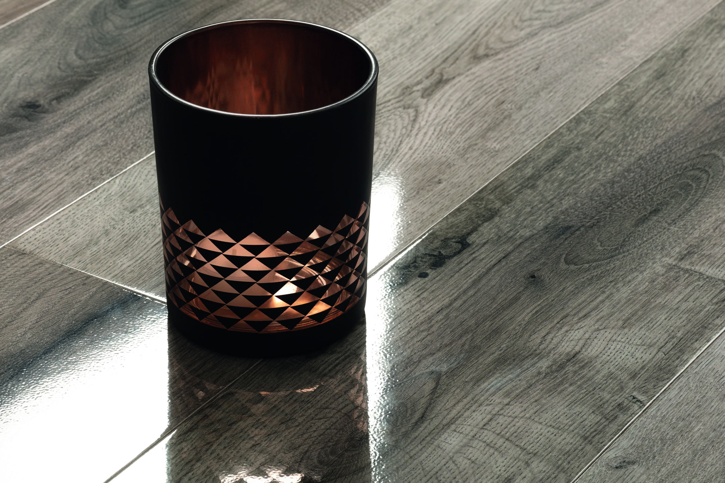 Candle and natural lighting reflected in the gloss of laminate flooring